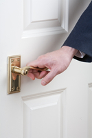 Close-up of Man's hand on door handle, studio shot