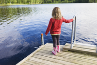 3 year old girl in red shirt on wooden dock looking at a lake, Sweden