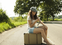 Teenage girl sitting on suitcase on the side of the road, looking at cell phone in summer, Germany