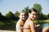 Close-up portrait of two girls sitting on beach at lake, looking at camera and smiling, Lampertheim, Hesse, Germany