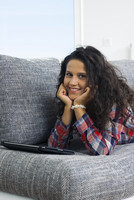 Close-up portrait of teenage girl at home, lying on sofa with tablet computer, looking at camera and smiling, Germany 11030041103| 写真素材・ストックフォト・画像・イラスト素材|アマナイメージズ