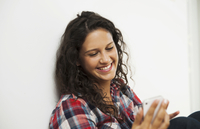 Close-up portrait of teenage girl looking at cell phone and smiling, Germany