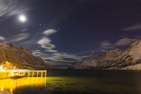 Boat and dock lit up at night with moon illuminating snow covered mountains at a fjord in the Arctic, Norway