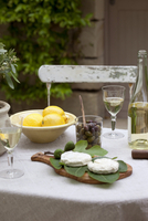 Close-up of table and chair in garden with appetizers and aperitif drink, Provence, France