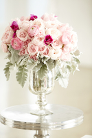 Bouquet of pink roses in silver vase on silver table, studio shot