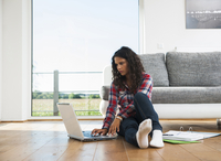 Teenage girl sitting on floor next to sofa, using laptop computer, Germany