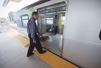 Man and Guide Dog Getting on Subway, Vancouver, British Columbia, Canada