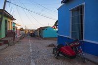 Motorcycle with sidecar parked along side colorful building on cobblestone street, Trinidad, Cuba, West Indies, Caribbean