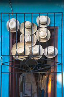 Close-up of straw hats displayed in doorway for sale, Trinidad, Cuba, West Indies, Caribbean