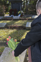 Backview of teenage boy placing flowere on grave stone in cemetery, Germany
