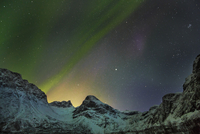 Polar light (Aurora Borealis) over Grotfjord at night, Kvaloya, Troms, Norway