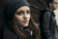Close-up portrait of teenage girl outdoors, wearing hat and headphones around neck, with young man in background, Germany 11030043798| 写真素材・ストックフォト・画像・イラスト素材|アマナイメージズ