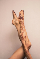 Woman's Legs and Arm Painted with Henna in Arabic Style, Studio Shot