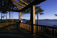 Woman Leaning on Railing, Holding Mug, Overlooking Ocean and Trees Tofino, British Columbia, Canada