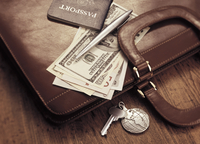 International Currency, Passport And Pen on Briefcase with Keys