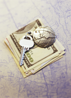 Key with Globe Keychain on Stack Of Currency on Map