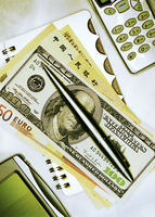 International Currency and Pen On Notepad with Cell Phone and Electronic Organizer