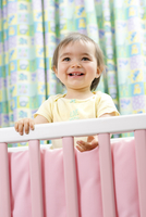 One year old baby girl standing in her crib, Chile