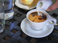 Cream being poured into coffee in white cup and saucer on outdoor, patio table, Canada