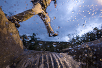 Low angle view of man jumping over a stream while hiking in New Hampshire, USA