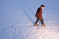 An elderly man walking in the snow using a cane, New England, USA