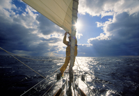 Man adjusting the jib while sailing offshore on the Atlantic Ocean.