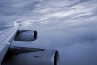 Close-up of the wing and engines of a jet while flying in the clouds