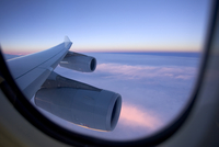 An aircraft wing and engines as seen from the window of a jet while flying above the clouds at sunset.