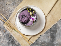 Lavender Noodle with Orchid Flower Garnish in Stone Bowl with Wooden Chop Sticks and Canvas Cloth, Studio Shot
