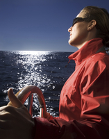 Woman Steering Boat while Sailing off Coast of Maine, USA