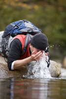Man Rinsing off Face to Cool Down after Hike, New Hampshire, USA