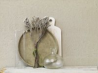 Still life of dried twigs with glass vase, platter and marble board.