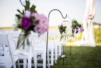 Flowers Hanging at End of Rows of Chairs at Wedding
