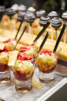 Close-up of Glasses of Fruit Cocktail and Chocolate Lollipops on Dessert Table