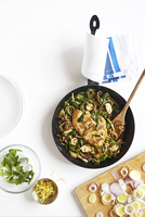 Skillet of Chicken, Arugula, Leeks, and Mushrooms with onions on cutting board, studio shot on white background