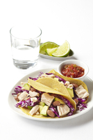 Tuna tacos with avocado, cabbage and beans on plate, with salsa, limes and a glass of water, studio shot on white background