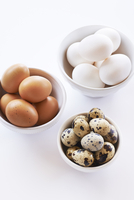 Brown and white Chicken Eggs and Quail Eggs in three bowls, studio shot on white background