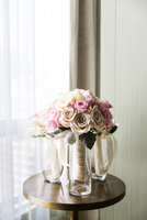 Bridal bouquets of pink and cream roses in vases on table by a window, Wedding Day preparations, Canada