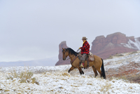 Cowboy Riding Horse in Snow, Rocky Mountains, Wyoming, USA