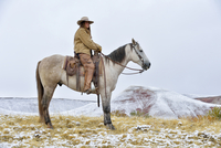 Cowgirl Riding Horse in Snow, Rocky Mountains, Wyoming, USA