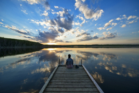 Hiker Sitting on Dock at Calm Lake at Sunset, Saskatchewan, Canada