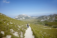 Man hiking on mountain trail, Gran Sasso mountain, Gran Sasso and Monti della Laga National Park, Apennines, Abruzzo, Italy
