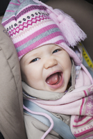 Close-up of Baby Girl Sitting in Car Seat wearing Winter Clothing