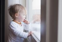 Portrait of Baby Girl Looking out Window 11030050750| 写真素材・ストックフォト・画像・イラスト素材|アマナイメージズ