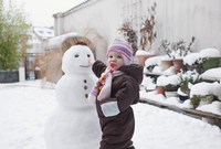 Baby Girl Playing with Snowman in Backyard
