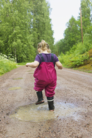 Young Girl Playing in Puddle, Sweden 11030051083| 写真素材・ストックフォト・画像・イラスト素材|アマナイメージズ