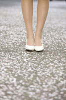 女性の足元と桜の花びら