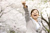 桜の下でガッツポーズをとる女性