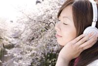 桜をバックに音楽を聴く女性