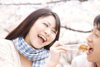 花見をしながらお弁当を食べるカップル